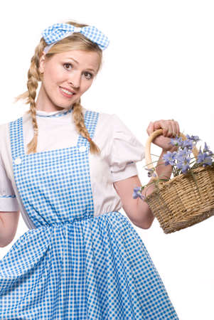 Attractive blond woman in braids wearing an old fashion little girl dress costume carrying a basket of wild flowers Imagens