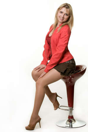 stool: Full body of a beautiful blond woman wearing mini skirt and red jacket sitting on a red stool over white