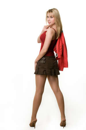 Full body of an attractive young blond woman wearing short cute brown skirt and red tank top with jacket off standing looking over shoulder on white Stock Photo
