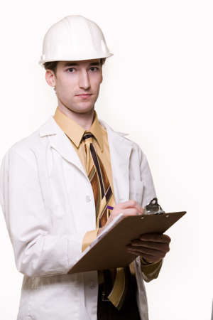 Young attractive man wearing white lab coat tie and a white hard hat holding onto a clipboard