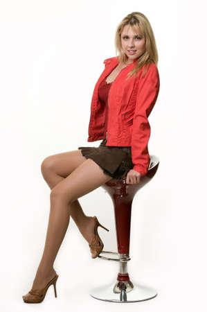 Full body of a beautiful blond woman wearing mini skirt and red jacket sitting on a red stool over white