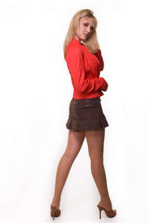 Full body of a beautiful blond woman wearing mini skirt and red jacket standing over white Banco de Imagens