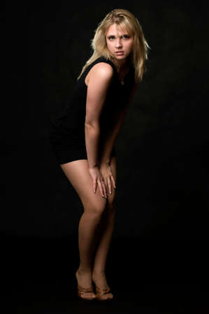 Full body of an attractive young blond woman wearing short black dress standing with hands on knees over black with hair back lit photo