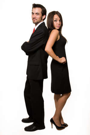 Full body of attractive young brunette man and woman man in black business suit and woman in black dress standing back to back over white
