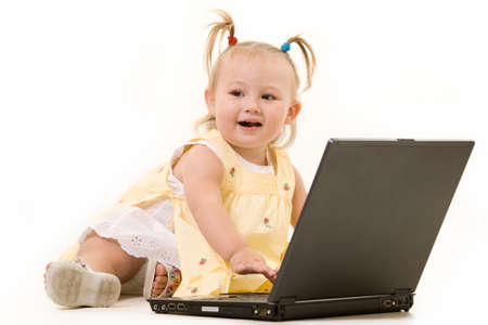 Adorable  girl toddler with pigtails in her hair sitting on the floor with a laptop computer over white Stock Photo - 3209329