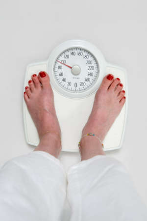 kilograms: Womans feet with red toe nails standing on a bathroom scale  Stock Photo