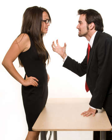 Attractive brunette woman and business man having a discussion each standing on opposite sides of a desk
