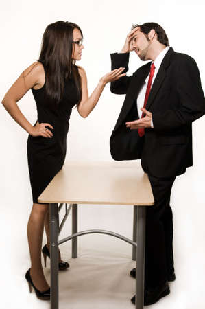 Attractive brunette woman and business man having a discussion each standing on opposite sides of a desk photo
