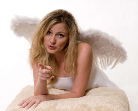sternly: Attractive blond woman wearing all white and angel wings looking sternly forward pointing her finger