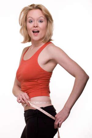 허리의 잘룩 한 선: Attractive blond woman wearing red and black workout attire measuring waistline with happy excited expression