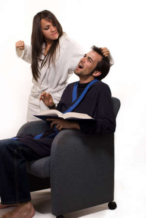 grabbing at the back: Young man wearing bathrobe sitting in a chair reading book with a woman in robe grabbing his hair with arm pulled back in a fist as if going to punch him