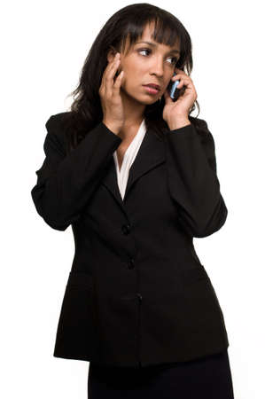 Attractive brunette Hispanic woman wearing business suit standing on white talking on cell phone with serious expression photo