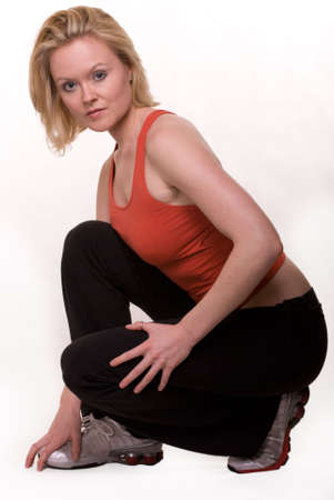squatting down: Full body of an attractive blond hair woman in red and black workout attire squatting down over white