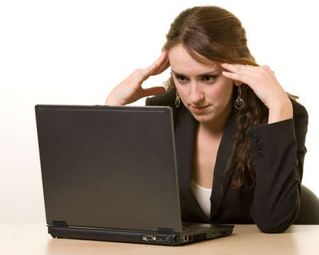 Attractive young brunette woman in business suit leaning on hands sitting at a desk looking bored or depressed photo