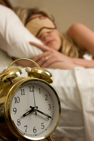 oclock: Blond woman sleeping in bed with eye cover on with focus on the alarm clock time being after eight oclock Stock Photo