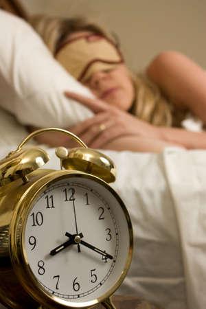 o�??clock: Mujer rubia durmiendo en la cama con cubierta de los ojos, con especial atenci�n a la alarma momento, despu�s de ocho
