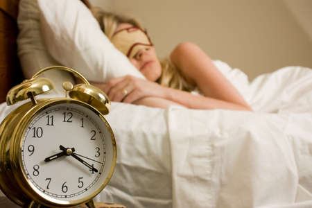 Blond woman sleeping in bed with eye cover on with focus on the alarm clock time being after eight o'clock Stock Photo - 3645967