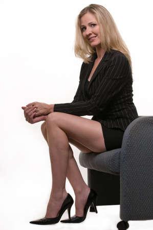 falda corta: Atractiva mujer rubia llevar traje corto con falda mostrando largo sentado con las piernas tobillos cruzados sonriente sobre blanco