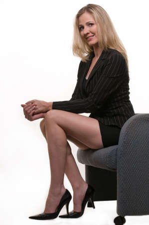 Attractive blond woman wearing business suit with short skirt showing long legs sitting with ankles crossed smiling over white