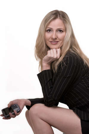 Attractive blond woman wearing business suit with short skirt with hand holding a cell phone sitting down smiling over white