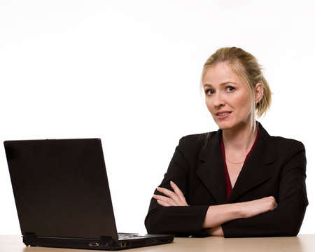 Attractive blond woman in business suit sitting at a desk with arms crossed in front of a computer looking forward over white