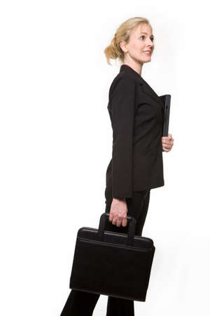 hair tied: Attractive blond hair woman wearing black business suit with hair tied up holding a laptop in arms and carrying a briefcase facing sideways about to walk