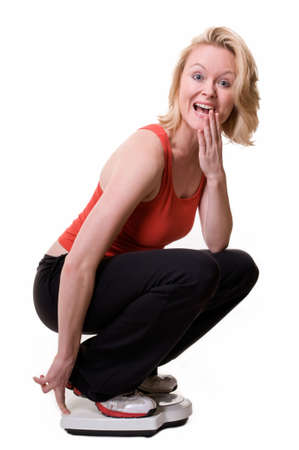squatting down: Attractive blond woman squatting down on a bathroom scale with happy excited expression and hand over mouth  Stock Photo