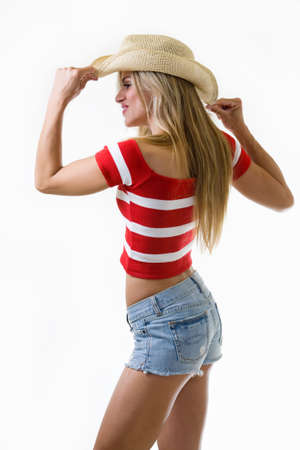 Portrait of an attractive blond woman wearing denim jean shorts and cowboy hat over white