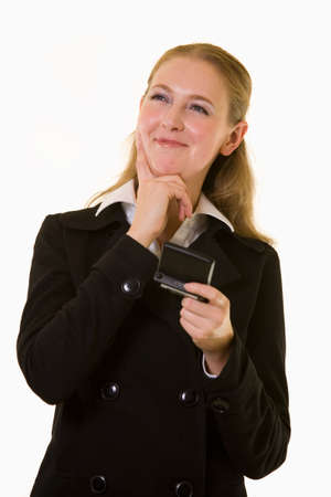 pager: Attractive blond woman in business attire holding a pager text messager with hand on chin and looking up as if thinking with a small smile on face standing on white Stock Photo