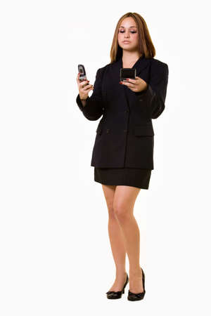 pager: Full body of a young attractive brunette woman wearing business suit standing while holding a pager text messaging  Stock Photo