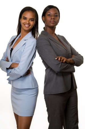Two African American business women with crossed arms wearing business attire standing over white