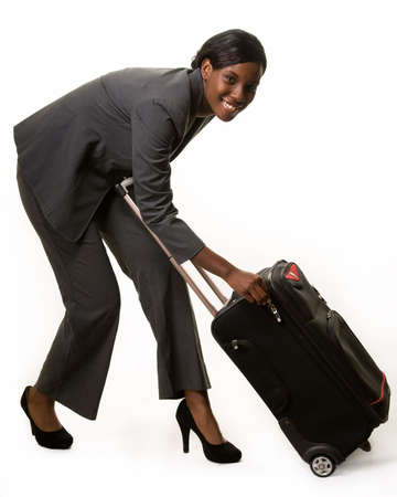 african american woman: Full body of African American woman in grey business suit bending over to open suitcase Stock Photo
