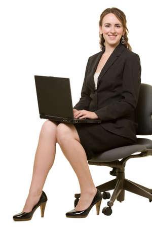 Full body of brunette caucasian woman wearing business skirt suit sitting holding laptop on knees over white smiling Stock fotó