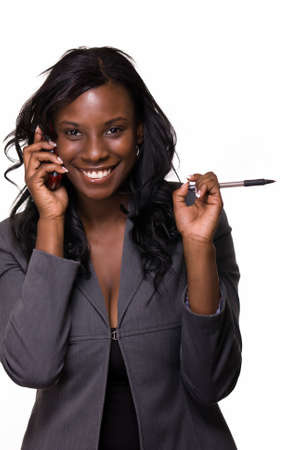 Attractive African American woman wearing business suit holding pen while talking on a cell phone smiling