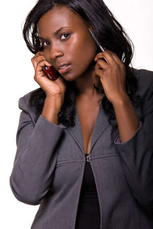 Attractive African american woman wearing grey business suit while talking on a cell phone photo
