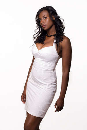 Attractive young African American woman wearing tight white dress over white