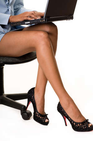 Legs of business woman sitting on a chair holding a laptop computer on her lap photo