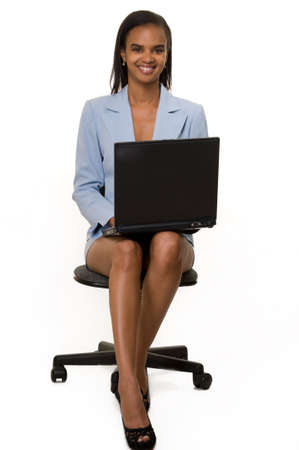 Attractive African American woman wearing light blue business skirt suit sitting and holding laptop on legs over white photo