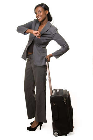 Full body of African American woman in grey business suit with black suitcase checking watch smiling standing on white photo