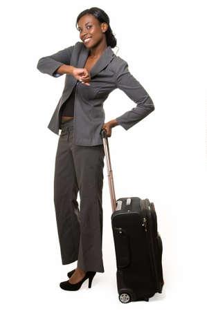 persona viajando: Todo el cuerpo de African American mujer en traje gris con negro maleta control de reloj sonriente de pie en blanco