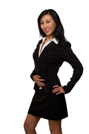 Attractive brunette Asian  woman wearing black business suit with skirt standing on white  photo