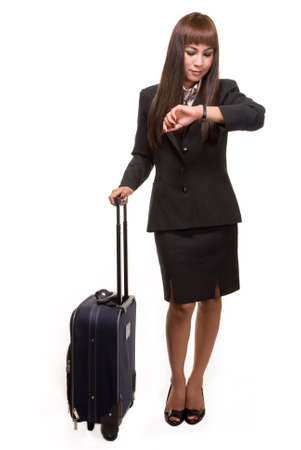 Full body of Asian woman in black business suit skirt with suitcase looking at wrist watch  photo