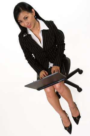 Full body of an attractive Asian woman wearing black business skirt suit sitting on chair and holding laptop on legs over white photo