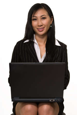 Attractive Asian woman wearing black business skirt suit sitting on chair and holding laptop on legs over white facing forward