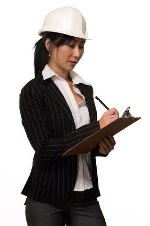 asian architect: Asian woman in business suit wearing a white safety hard hat holding and writing on a chart