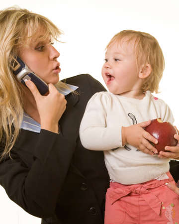 Attractive blond woman in business attire talking on cell phone carrying a cute baby girl with an apple looking at each other with cute expression
