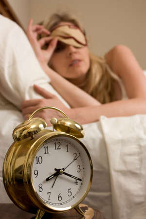 Blond woman sleeping in bed peeking out from cover over eyes looking at the time on a round gold alarm clock time is after eight o'clock  Stock Photo - 3791365