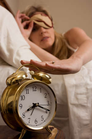 Blond woman sleeping in bed peeking out from cover over eyes looking at the clock and reaching to turn off a round gold alarm clock time is after eight o'clock  Stock Photo - 3791372