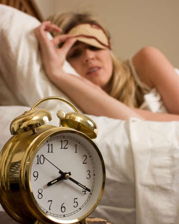 Blond woman sleeping in bed peeking out from cover over eyes looking at the time on a round gold alarm clock time is after eight o'clock Stock Photo - 3791362