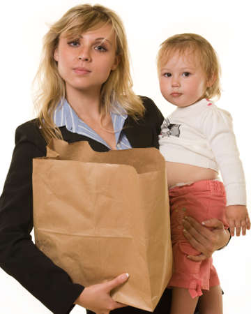 Attractive blond woman in business attire carrying a grocery bag in one arm and baby in the other showing busy mother photo